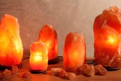 Himalayan salt lamp on wooden base - natural rough shape